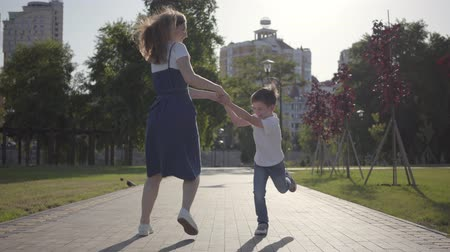 братья и сестры : Joyful older sister spinning around with younger brother holding hands in the summer park. Leisure outdoors. Friendly relations between siblings. Carefree kids having fun together Стоковые видеозаписи