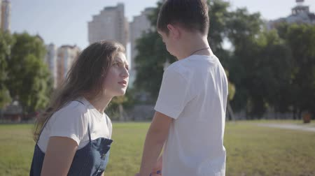perseguição : Relationship between siblings. Older sister scolding her younger brother in the summer park. Naughty boy walking with his sister outdoors. Stock Footage