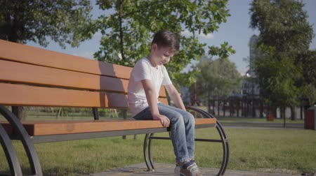 schoolyard : Sad lonely little boy sitting on the bench in the park. Cute child spending time alone outdoors. Summertime leisure