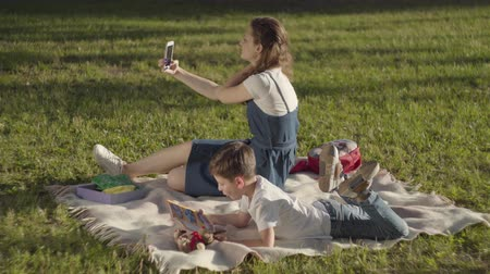 портретный : Older sister spending time with younger brother outdoors. The boy reading the book and girl taking selfie in the park. Summer leisure. Gadget addiction