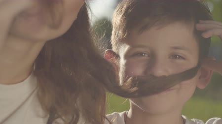 bigodes : Close-up portrait of older sister spending time with younger brother outdoors. The boy and girl making false mustaches with hair of the girl in the park. Summer leisure. Siblings have fun together Stock Footage