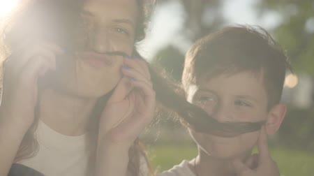 bigodes : Portrait of older sister spending time with younger brother outdoors. The boy and girl making false mustaches with hair of the girl in the park. Summer leisure. Siblings have fun together Stock Footage