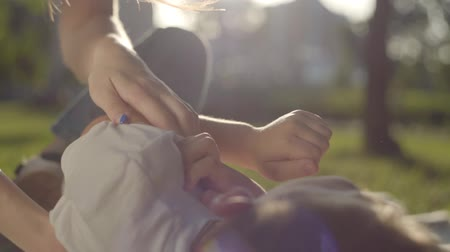 любовь : Close-up hands of older sister tickling younger brother in the park. The boy and girl spending time together outdoors. Summer leisure Стоковые видеозаписи