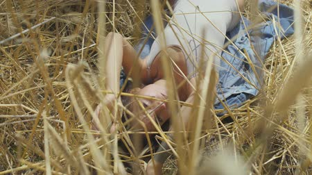 gwóżdź : Cute woman wearing bodysuit with short hair lying on the wheat field. Girl enjoys nature looking and posing at the camera. Confident carefree girl outdoors. Real people series Wideo