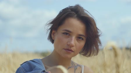 gwóżdź : Portrait stylish woman with short hair relaxing on the wheat field. Girl enjoys nature looking and posing at the camera. Confident carefree girl outdoors. Real people series Wideo