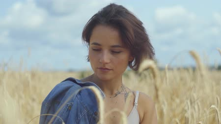 gwóżdź : Portrait of an attractive woman with short hair with jeans jacket standing on the wheat field looking at camera close-up. Connection with nature, natural beauty