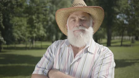 grandad : Confident old gray bearded man in straw hat looking at camera smiling standing in the park. Leisure outdoors. Mature man resting in the summer garden. Healthy cheerful senior retired man