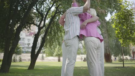 piada : Two cute mature couples hugging and spinning around in the park together standing in circle. Friendly company resting outdoor. Old men and women smiling happily. Healthy cheerful senior retired people