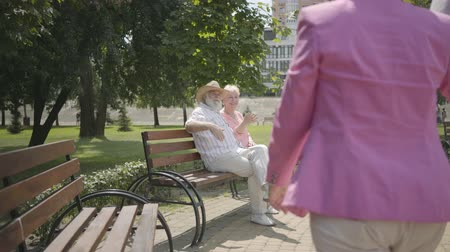 grandad : Two positive mature couples meet in the park. Double date of senior couples. Old men and women greeting each other, man shake hands, women hugging. Healthy cheerful senior retired people.