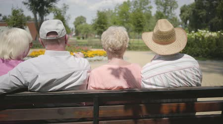grandad : Two adorable mature couples sitting on the bench and talking together. Mature people resting outdoors. Cheerful senior retired people. Back view.