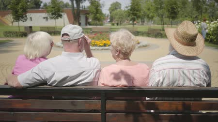 grandad : Two cute mature couples sitting on the bench and talking together. Mature people resting outdoors. Cheerful senior retired people. Back view.