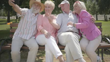 grandad : Two cute mature couples sitting on the bench together. The old man taking a selfie of company in the park. Mature people resting outdoors. Summertime leisure. Cheerful senior retired people. Stock Footage