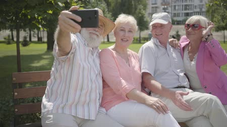 grandad : Two cute fun adult couples sitting on the bench together. The old man taking a selfie of company in the park. Mature people resting outdoors. Summertime leisure. Cheerful senior retired people.