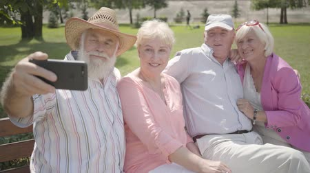 grandad : Two adorable joy adult couples sitting on the bench together. The old man taking a selfie of company in the park. Mature people resting outdoors. Summertime leisure. Cheerful senior retired people.
