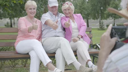 mates : Old man in a hat makes a photo of his friends sitting on a bench in the park. Two adorable joy women and man resting outdoors together. Cheerful senior retired people.