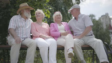 mates : Two cute mature couples talking and smiling sitting on the bench in the summer park. Double date of senior couples. Friendly company resting outdoors. Old men and women met together. Retired people. Stock Footage