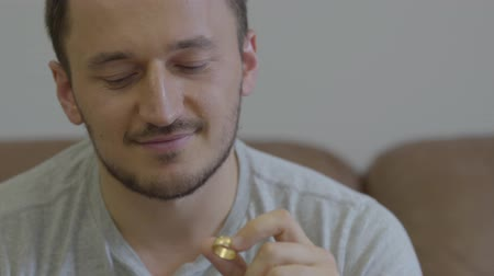 запомнить : Portrait of the happy man holding golden wedding ring smiling sitting at home. The guy going to make a proposition for his girlfriend or remembers the pleasant moments of family life.