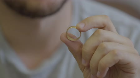 remember : Portrait of unrecognized bearded man holding golden wedding ring sitting at home. The guy going to make a proposition for his girlfriend or remembers the pleasant moments of family life. Stock Footage