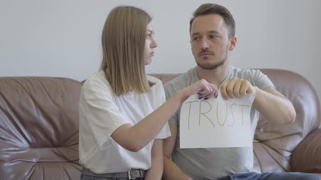 zdrada : Man and woman tearing apart the word trust written on the paper. Problems in the relationship between man and woman. Betrayal, mistrust, breakup concept Wideo