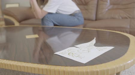 ex boyfriend : Unrecognizable crying woman on the background of torn childrens drawing with the image of mom and dad lying on the table. Betrayal, mistrust, breakup concept Stock Footage