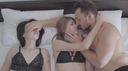 kochanka : Handsome man lying in bed with two beautiful caucasian girls. Bearded man kisses a blonde and closes his eyes brunette. Love threesome. Polygamy, polyamory Wideo