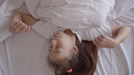 duracion : Adorable small girl sleeping in the bed at home. Girl waking up from an alarm clock on her smart watch. Modern technology. Carefree childhood.