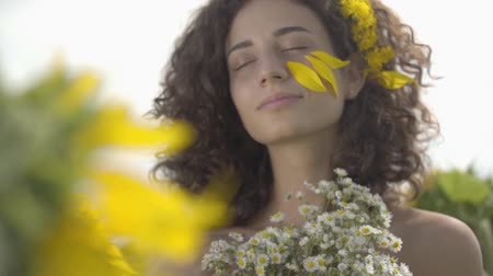 рыжеволосый : Portrait of a pretty curly girl looking at the camera smiling standing in the sunflower field with bouquet of wildflowers. Bright yellow color. Freedom concept. Happy woman outdoors. Slow motion.