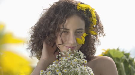 fragrances : Portrait of a cute curly girl looking at the camera smiling standing in the sunflower field with bouquet of wildflowers. Bright yellow color. Freedom concept. Happy woman outdoors. Slow motion.