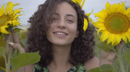 рыжеволосый : Portrait of cute curly girl looking at the camera smiling covering her face with two sunflowers in the sunflower field. Bright yellow color. Connection with nature. Rural life. Slow motion Стоковые видеозаписи