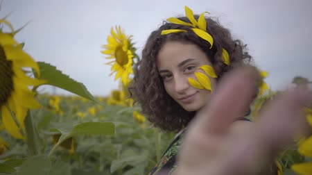 привлекать : Portrait of beautiful curly girl inviting, attrakting viewer in the sunflower field. Bright yellow color. Connection with nature. Rural life. Slow motion