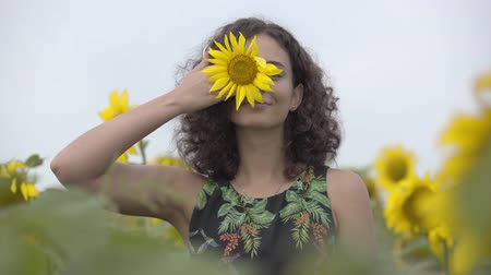 рыжеволосый : Pretty curly playful smiling girl standing on the sunflower field. Bright yellow color. Freedom concept. Happy woman outdoors
