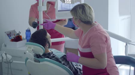 dikkatli : Dentist in medical mask and gloves checking the mouth of the patient using a mirror. Assistant bringing the instrument to doctor. Stomatologist at work in the office. Dental treatment, medical concept Stok Video