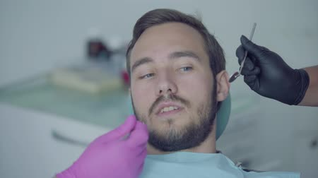 ortodonta : Close-up portrait of young scared man in the dentist office covering mouth with hands. Hands of the doctor and nurse showing to the patient medical tools. Dental treatment, medical concept. Wideo