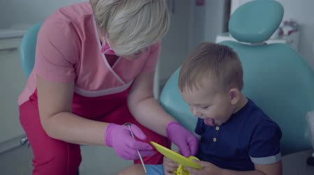 yenirce : Dentist in medical mask and gloves ready to checking tooths of little carefree boy sitting with mirror in the chair. Female professional doctor stomatologist at work. Dental treatment, medical concept