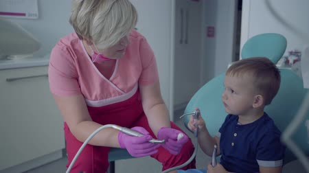 fearless : Dentist in medical mask and gloves ready to checking tooths of little carefree boy sitting in the chair. Female professional doctor stomatologist at work. Dental treatment, medical concept.