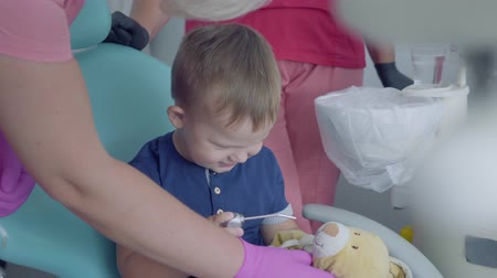 yenirce : Cute small child playing with medical tools sitting in the chair in the dentist office. Carefree child visiting doctor. Boy plays at the dentist. Dental treatment, medical concept. Dental care. Stok Video