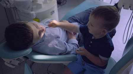 fearless : Little boy playing a doctor and teenage guy sitting in the chair in dentist office. Child inspecting teeth of boy. Kid playing a doctor. Dental treatment, medical concept. Dental care.