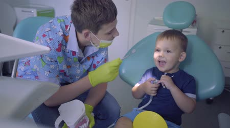 ortodonta : Skill boy medical mask and gloves and little child playing in dentist office. Young guy teaching the kid to brush teeth to the jaw mock. Dental treatment, medical concept. Dental care. Wideo