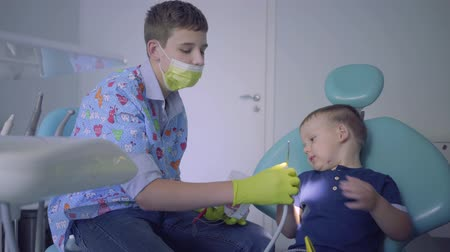 fearless : Teenage boy medical mask and gloves and little child playing in dentist office. Young guy teaching the kid to brush teeth using the jaw mock. Dental treatment, medical concept. Dental care.