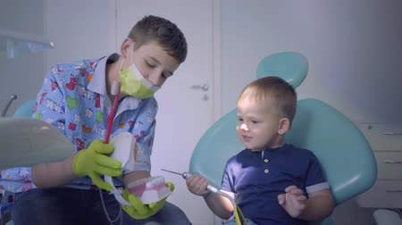 stomatologia : Teenage boy and his little brother playing in dentist office. Older brother teaching the boy to brush teeth using the jaw mock. Dental treatment, medical concept. Dental care.