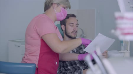 ortodonta : Female dentist in pink mask and gloves showing to male patient picture of his teeth on the screen. The young man visiting the doctor. Dental treatment, medical concept. Dental care.