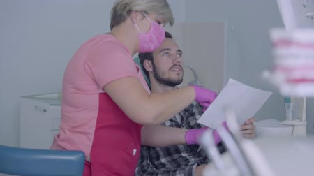stomatologist : Female dentist in pink mask and gloves showing to male patient picture of his teeth on the screen. The young man visiting the doctor. Dental treatment, medical concept. Dental care.