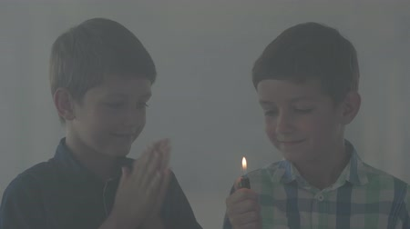 minor : Two little brothers playing with the lighter in the dark smoky room. One boy lit the lighter with smile. Children play with fire. Arson minors Stock Footage