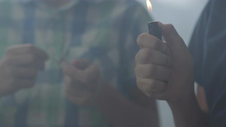 arson : Two unrecognized little brothers playing with fire in the dark smoky room. One boy lit the lighter in the background another lit a match in the foreground. Children play with fire. Arson minors Stock Footage