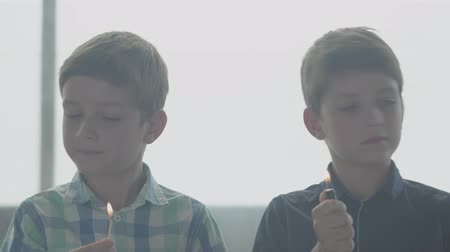 minor : Two little twins brothers playing with the fire in the smoky room in front of a window. Kids putting out match and lighter and shaking heads. Children teach not to play with fire. Concept of danger
