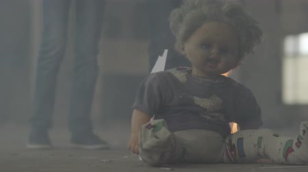 destruído : Legs of two boys in the dark room in the cloud of smoke in the background. Scary dirty doll burning on the floor in the foreground. Concept of fire, flammability, non-compliance with safety rules