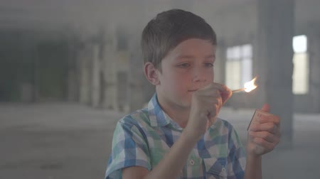 arson : Portrait of a cute boy setting fire to a match while standing in a smoky room.