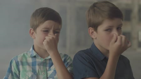 füstös : Two confused scared boys standing in the smoky room closing their noses with hands. Concept of danger. Fire, flammability, non-compliance with safety rules