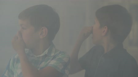 zapalovač : Two confused scared boys standing in the smoky room closing their noses with hands. Concept of danger. Fire, flammability, non-compliance with safety rules