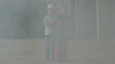 infância : Two little boys in white safety helmets stand next to a fire extinguisher in a smoky room. Concept of fire, flammability, non-compliance with safety rules.